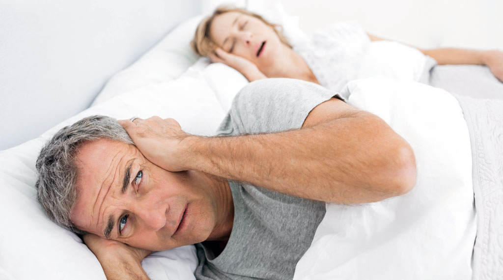 Couple In Bed With Man Bothered By Wife Snoring